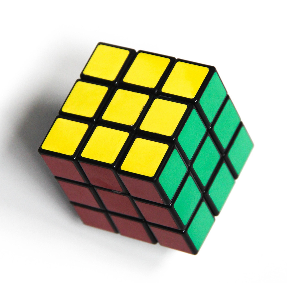 A rubik cube with the completed yellow, green and red sides facing the camera.