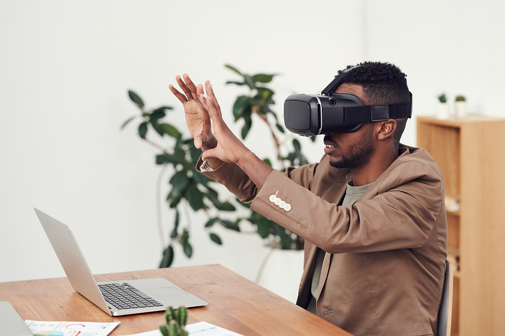 A man wearing a VR headset has his laptop open on a table and his arms outstretched in the air in front of him.
