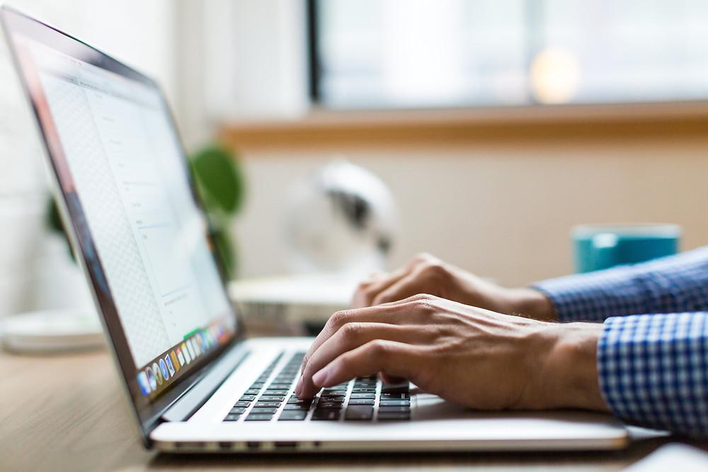 Man in shirt typing on laptop
