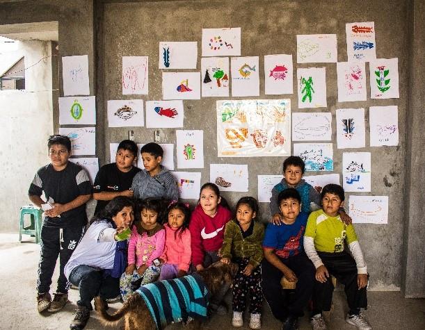 Blanca Cancharis, profesora del taller, y los niños y niñas participantes del taller exponiendo sus dibujos al finalizar el taller.