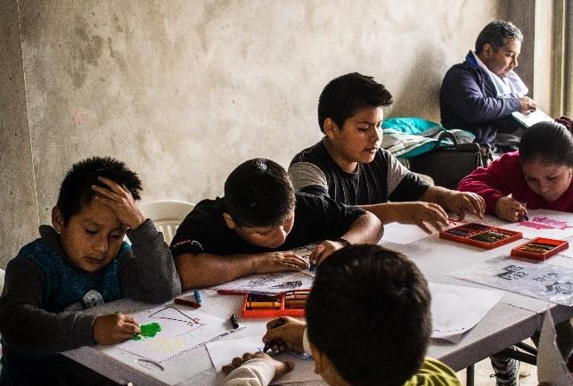 Niños y niñas del albergue «Señor de los Milagros» haciendo sus primeros trazos en el taller de dibujo.