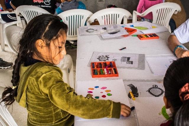 Anita, 5 años, experimentado con los colores durante el taller de dibujo.