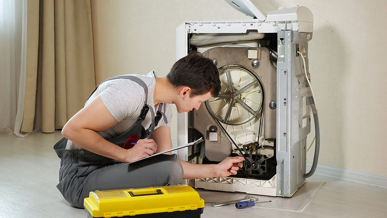 young serviceman checks broken washing machine loader with open back side panel on floor i