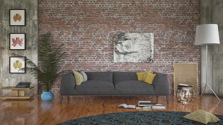 A grey sofa against an exposed brick wall