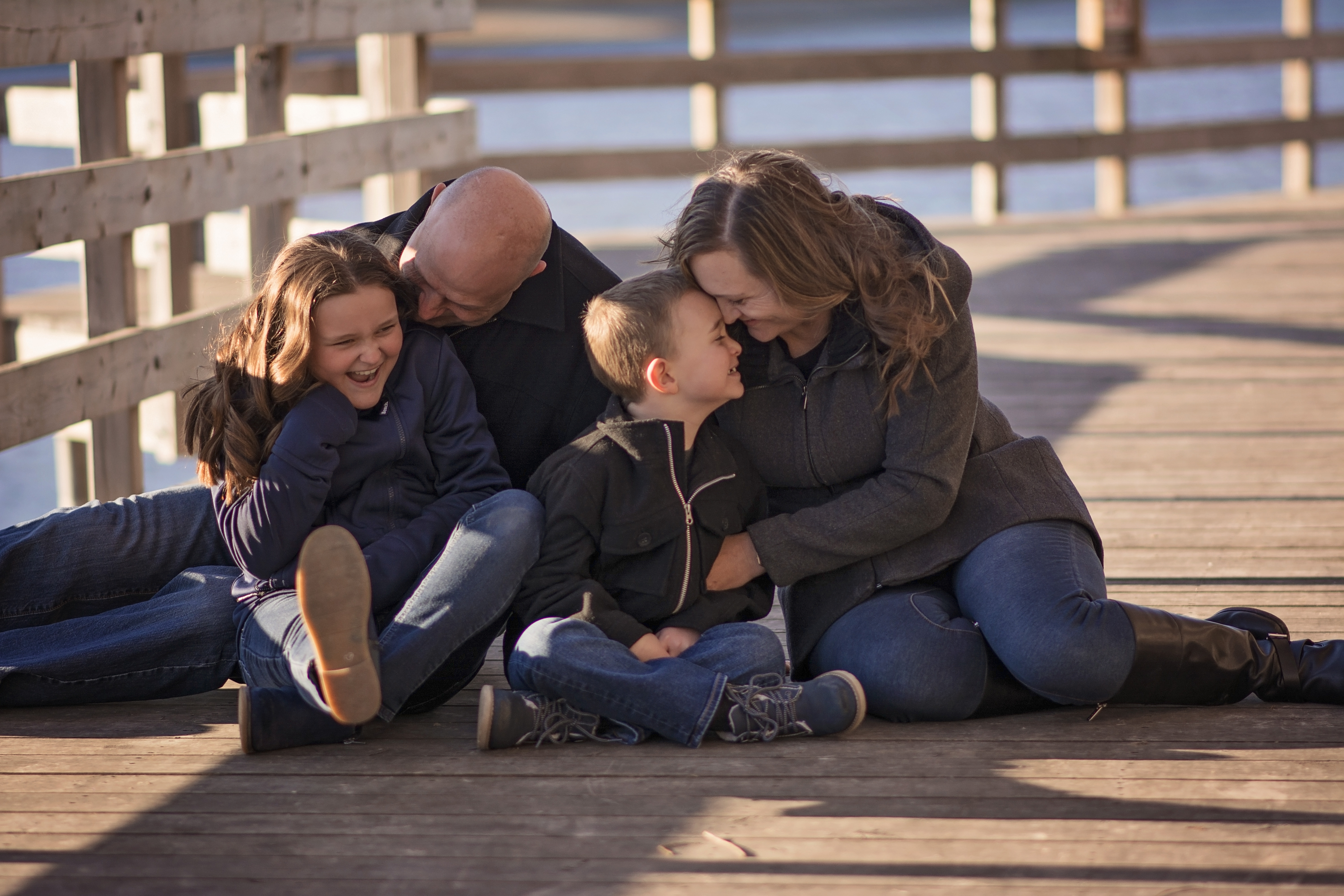 family snuggling on bridge