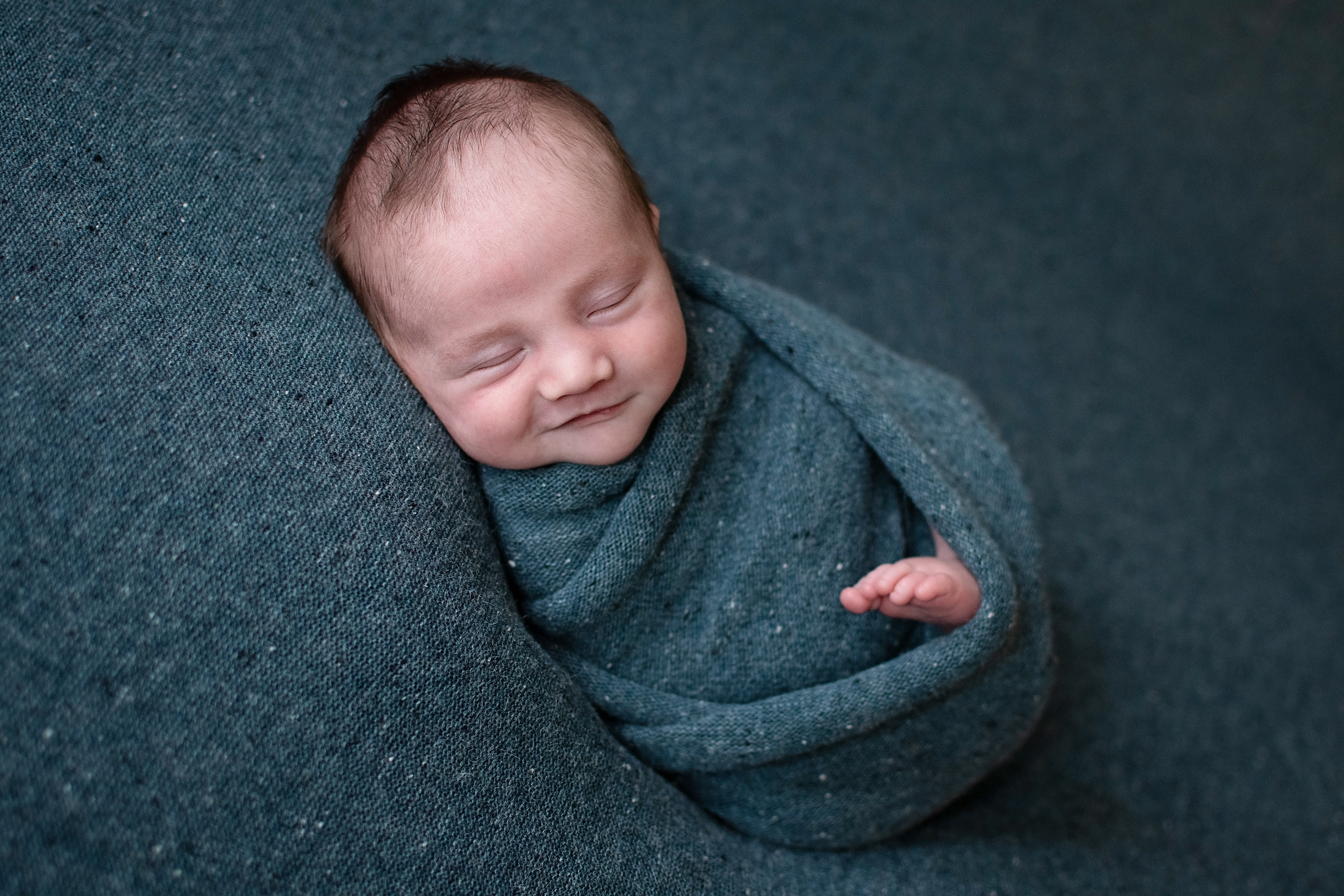 Newborn wrapped smiling