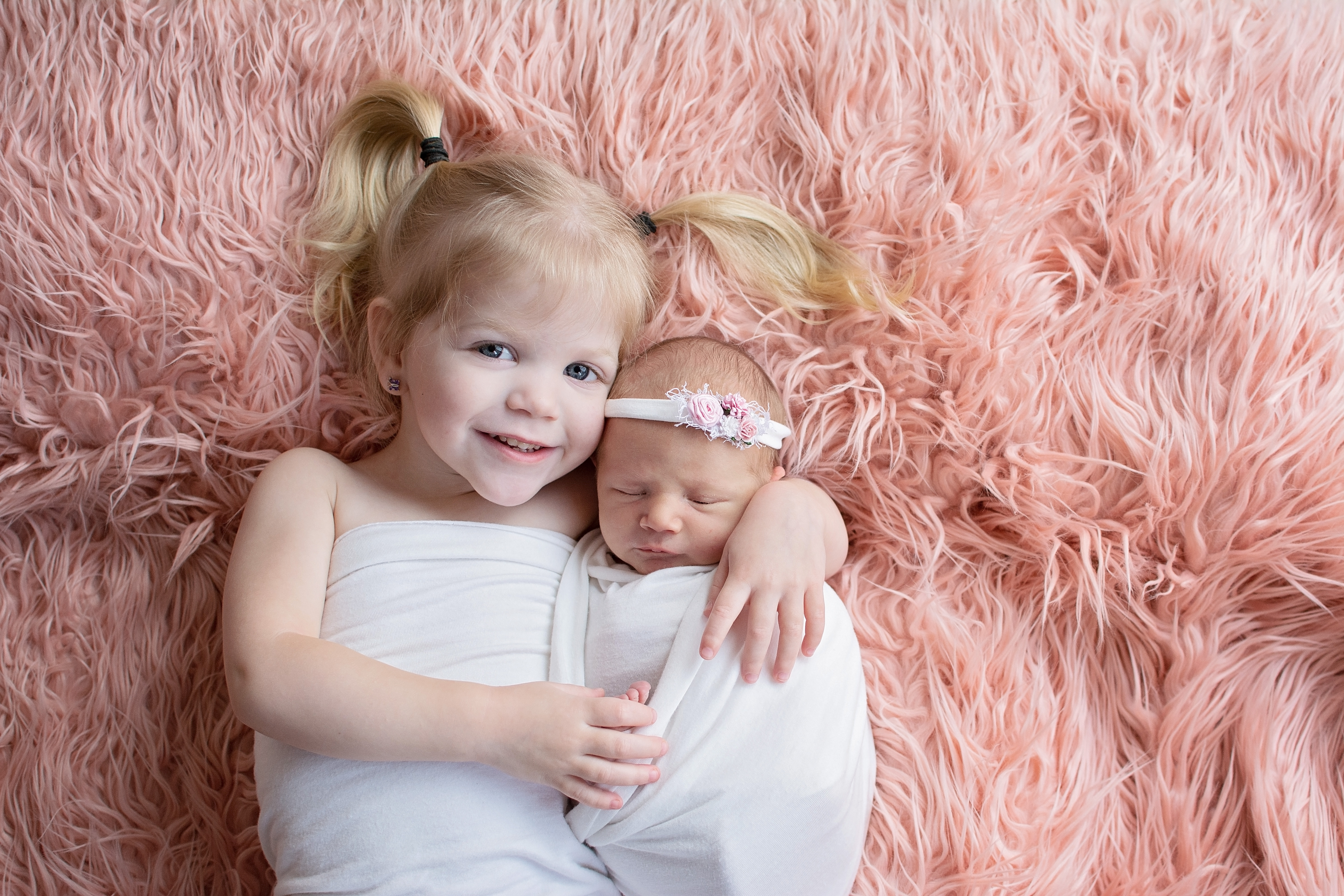 sibling posed with newborn girl