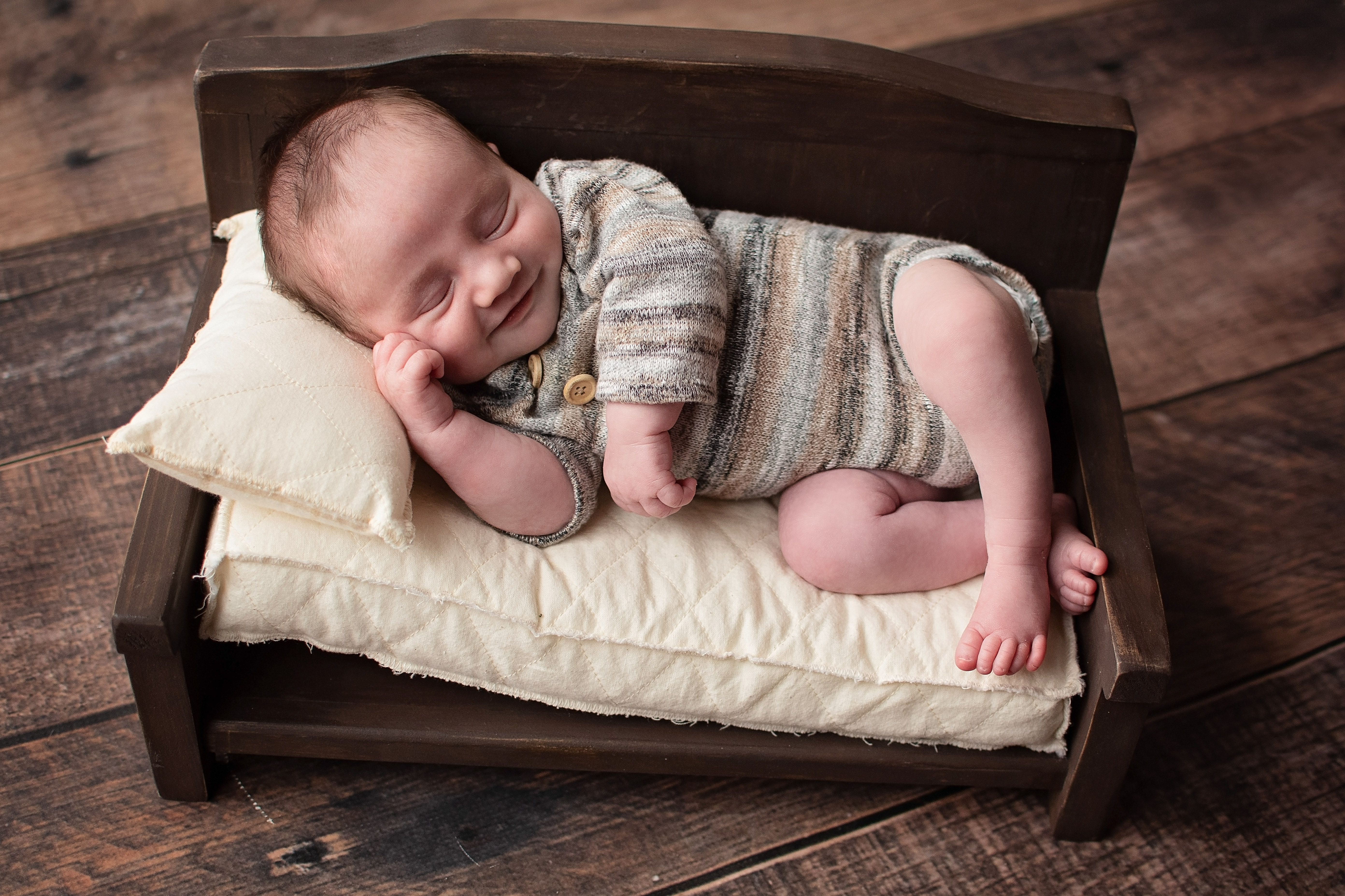Newborn on bed smiling