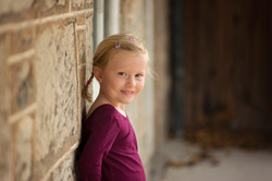 little girl leaning up a wall