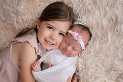 smiling newborn baby girl with sibling