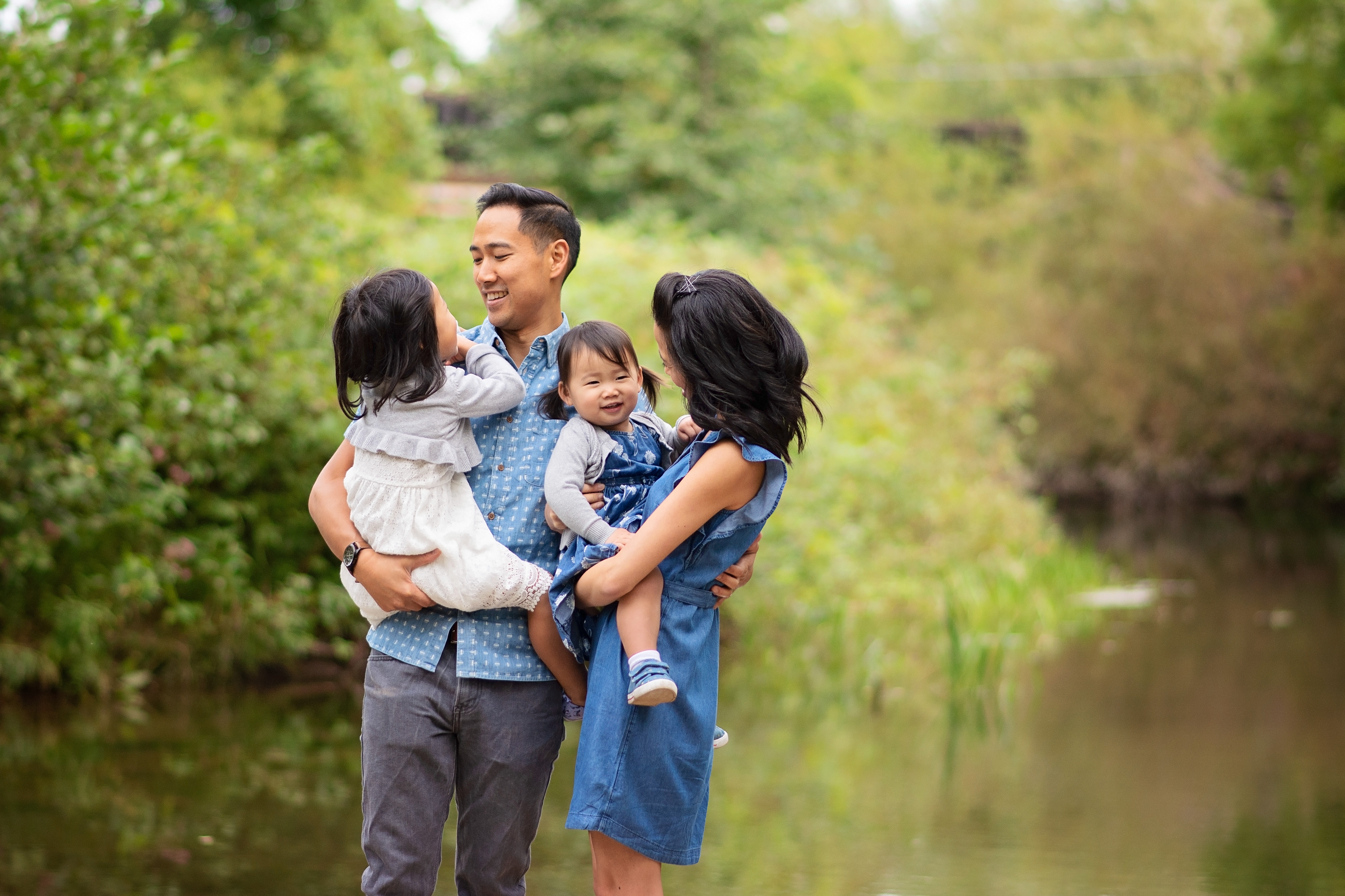 family laughing next to a river
