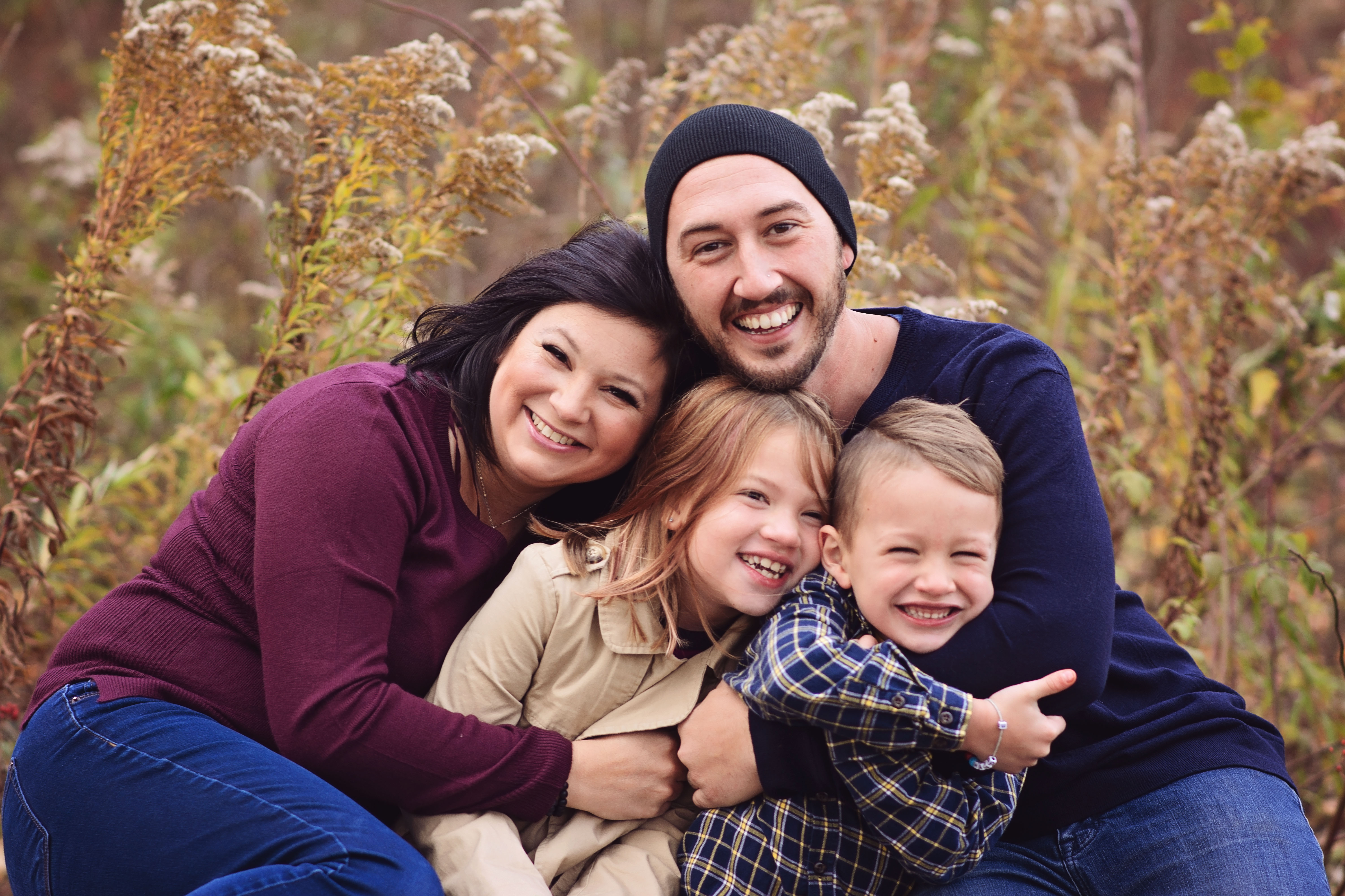 family posed hugging during fall