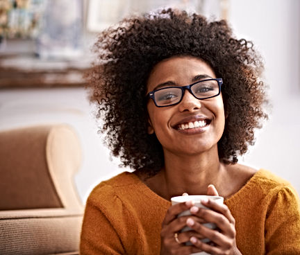 black woman with afro, navy blue glasses, spectacles, orange jumper, french manicure nails, threaded eyebrows, holding cup of coffee, beaming smile