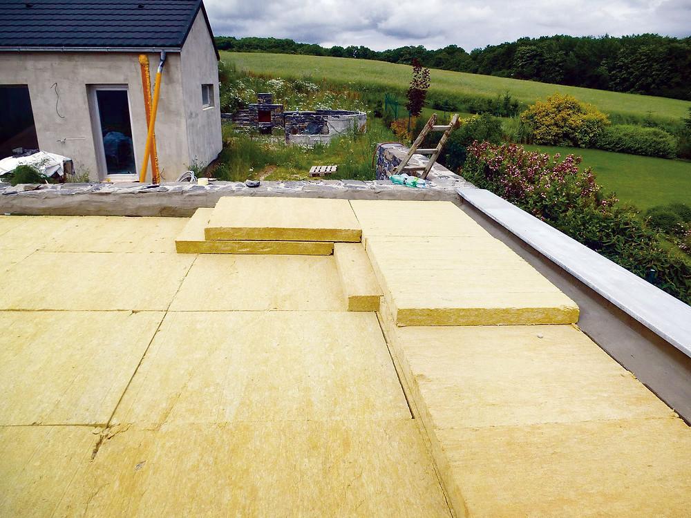 Plochá střecha na obrázku využívá k závlaze speciální nasákavou minerální vlnu, která zásobuje rostliny vodou. Je osázena nenáročnými rozchodníky, které vydrží dlouhou dobu bez zalévání i v horkých letních měsících.