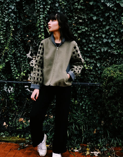 Woman wearing Alpaca Bomber jacket in front of ivy wall.