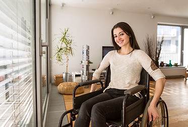 Young disabled woman in wheelchair at ho