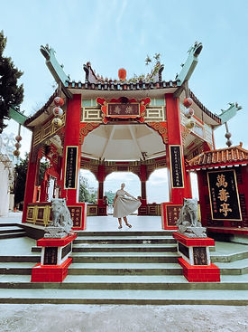 girl standing in red chinese temple gate