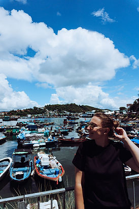girl standing in front of harbour with small fishing boats
