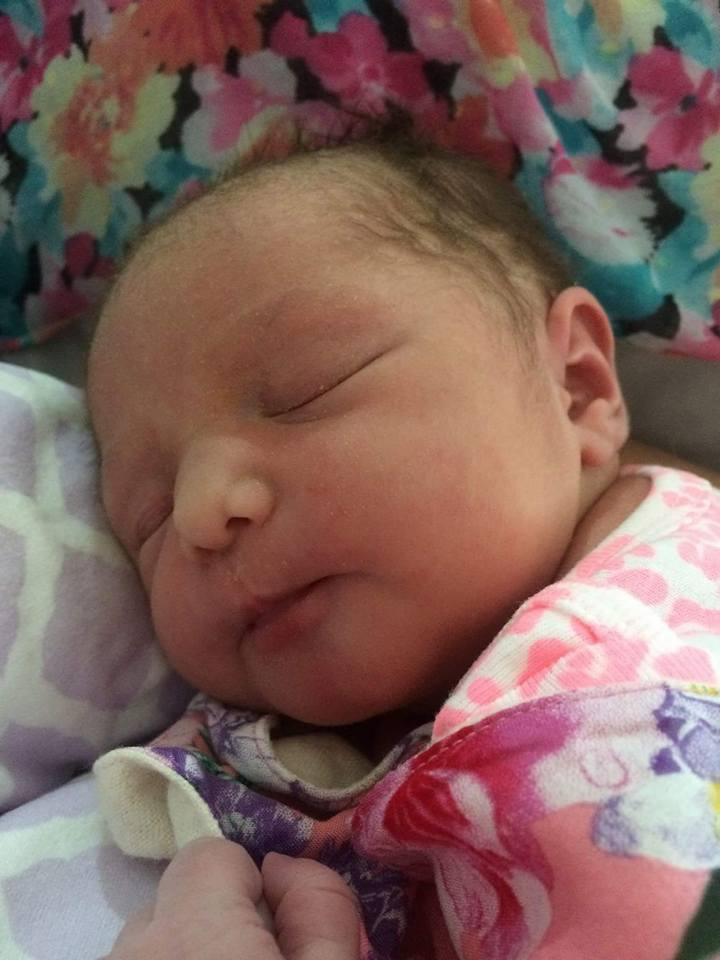 A newborn baby sleeping wearing a floral bib.