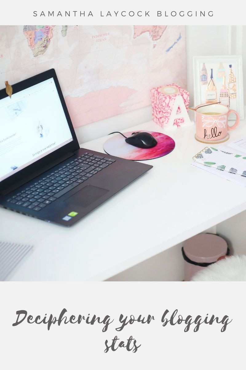 A desk with a laptop and mouse on it with a pink coffee mug.