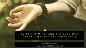 A person in a mediation pose with a mala on their wrist.