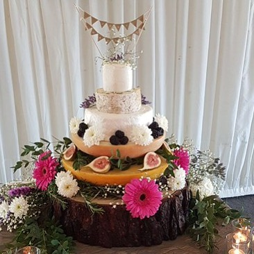 Large wood cake stand with cheese.