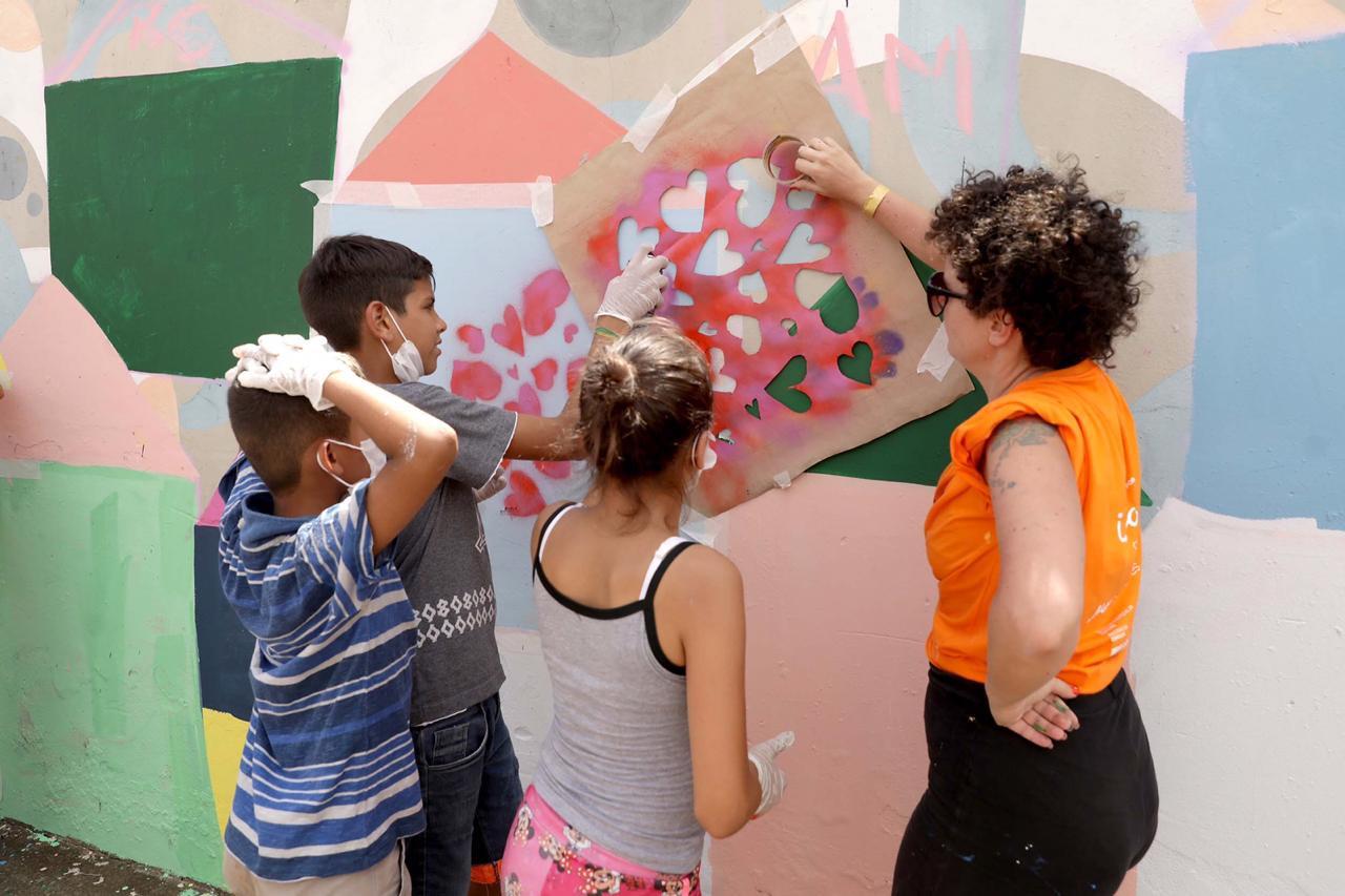 aplicando stêncil no muro com as crianças em Jundiapeba