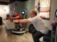 Two Male Members Holding a Sumo on a vibration machine