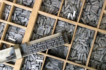 Un composteur posé sur une casse (tiroir) contenant  les caractères mobiles