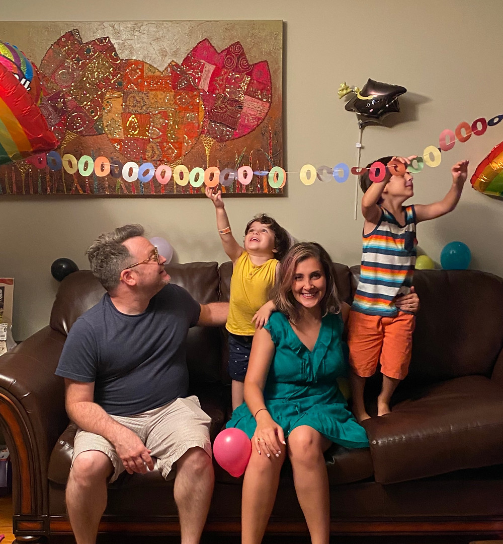 Author Sarvenaz Tash with her family, including her two young children jumping on the couch.