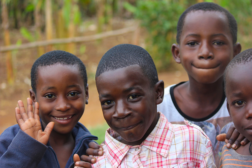 Four young kids smiling looking into the camera.