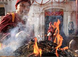 Buddhist monk peering through the smoke of a holy fire outside Boudhanath Stupa