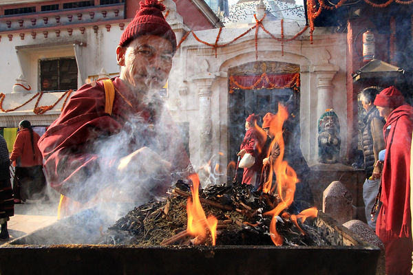 Monk burning saced incense and offering blessing at Boudhanath Stupa, Kathmandu, Nepal