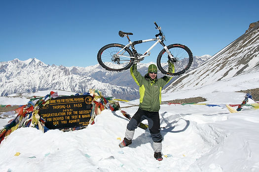 Cyclist raising mountain bike aboe his head at the top of Throng La pass, Nepal