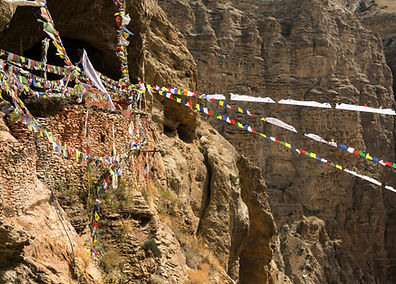Cave entrance with prayer flags, Upper Mustang, Nepal