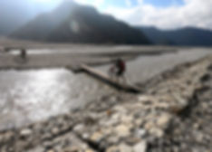 Walking mountain bike on makeshift timber bridge across Kali Gandaki River, Mustang