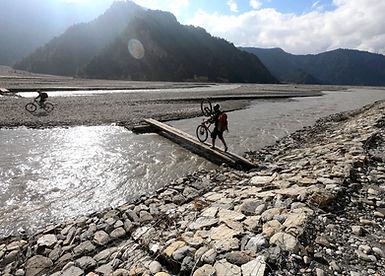 Walking mountain bike on makeshift timber bridge across Kali Gandaki River, Mustang