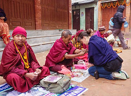 Woman receiving blessing from Buddhist monk in Bouhanath, Nepal