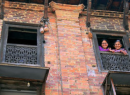 Two Newari women looking outthe window of their traditional home in Bhaktapur, Nepa
