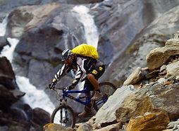 Mountain bike rider navigating boulders riding down mountain in Mustang, Nepal