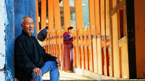 Old man sitting on bridge to a Dzong, Bhutan