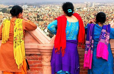 Three Nepalese women in saris, look at view of Kathmandu from Swaymbhunath Temple, Nepal