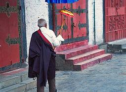 Old man spinning large prayer wheel while walking the kora around the Barkhor in Lhasa, Tibet