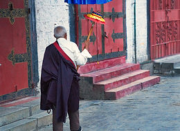 Old man spinning large prayer wheel while walking the kora around the Barkhor in Lhasa, Tibet