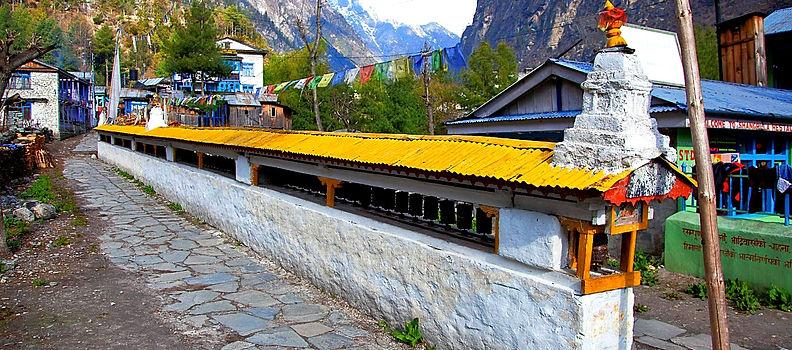 Mani wall and prayer wheel leading into Chame village, Nepal