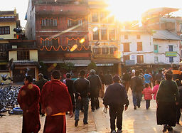 Buddhist monks and pilgrims walking around Boudhanath Stupa in the early morning