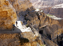 Mountain bike riders climbing narrow trail in gorge in Upper Mustang, Nepa.