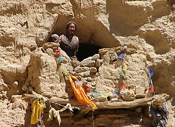 Woman at entrance of cave in Upper Mustang, Nepal