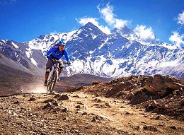 Mountain bikeriderracing down valley with mountains behind in Upper Mutang, Nepal