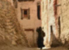 Woman walking in alleyway in Lo-Manthang, capita of UpperMutang, Nepal
